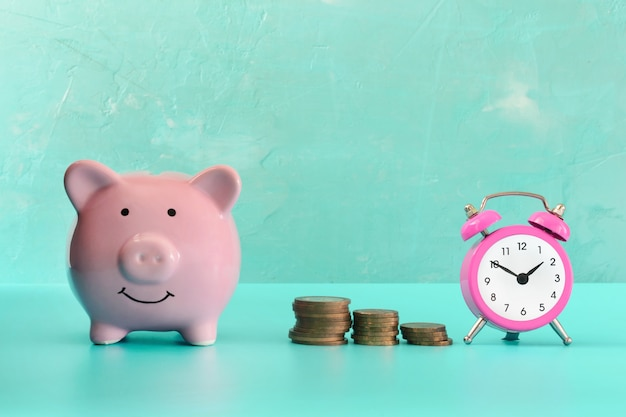 Between the piggy bank and a small pink alarm clock, three stacks of coins are in order.