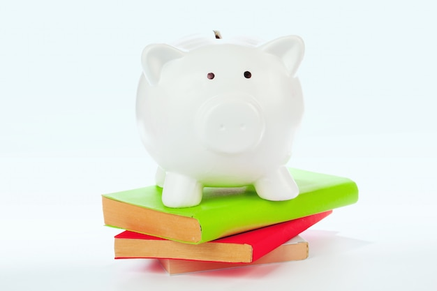 Piggy bank over a stack of colorful books
