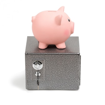 Piggy bank standing on a safe