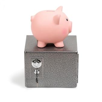 Piggy bank standing on a safe