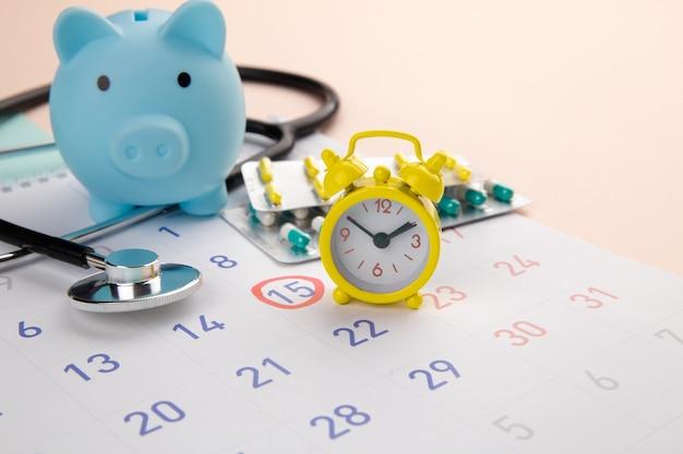 돼지 저금통, 청진기, 알람 시계 및 달력 테이블