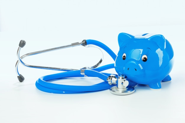 Piggy bank and stethoscope isolated on a white