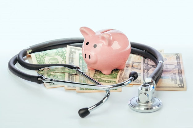 Piggy bank and stethoscope isolated