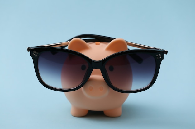 Piggy bank in sunglasses on a blue