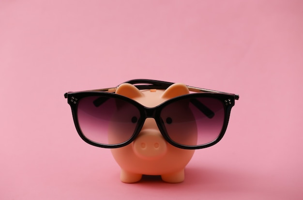 Piggy bank in sunglasses on a pink