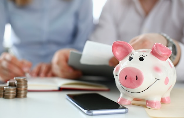 Piggy bank on table aganist home background