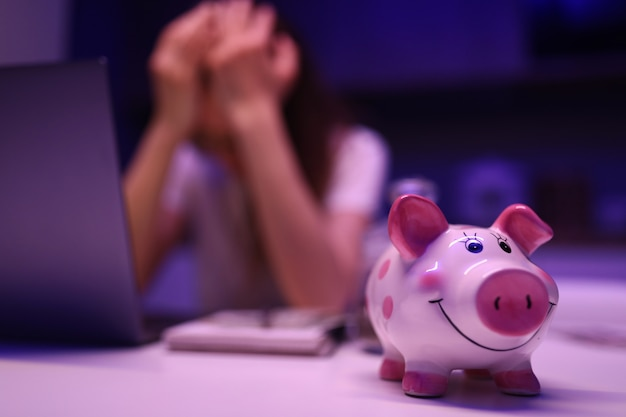 Piggy bank on table, an upset woman sits behind