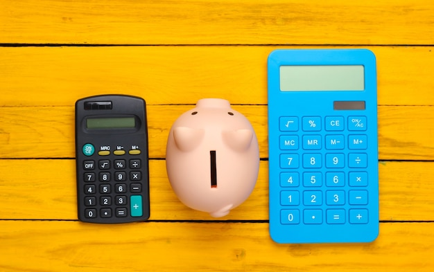 Piggy bank and two calculators on a yellow wooden surface. top view