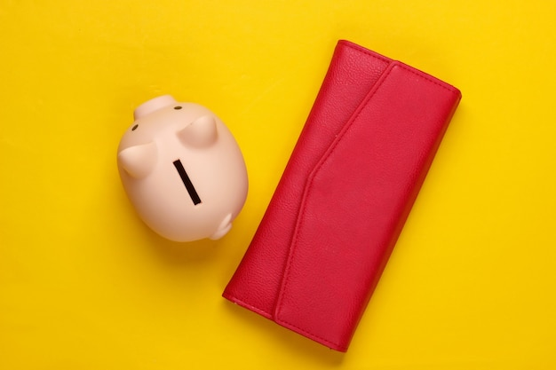 Piggy bank and wallet on yellow