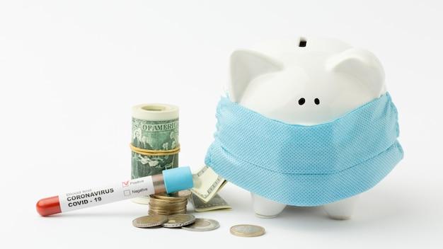 医療マスクとコロナウイルステストを身に着けている貯金箱