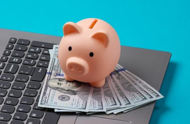 Piggy bank with 100 dollar bills on laptop keyboard closeup