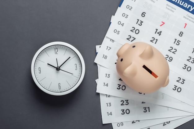Копилка с ежемесячным календарем, часы на серой поверхности. месячный бюджет. вид сверху