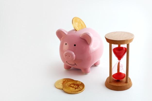 孤立した白い背景の上のビットコインコインと砂時計と貯金箱