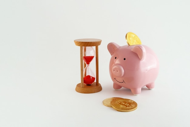 Piggy bank with bitcoin coins and hourglass on isolated white background