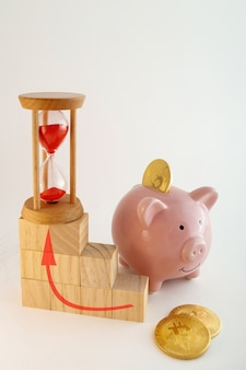 Piggy bank with bitcoin coins, hourglass and wood cubes growing graphic on isolated white background