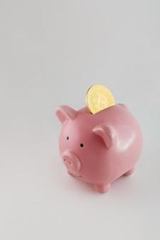 孤立した白い背景の上のビットコインコインと貯金箱