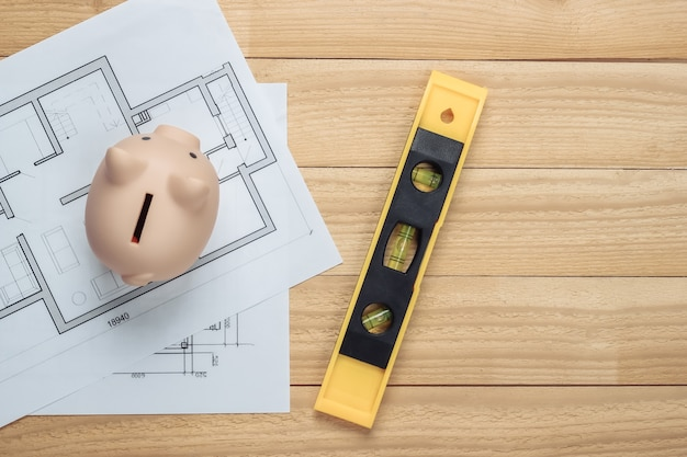 Piggy bank with blueprint, level on wooden boards. house building costs. top view