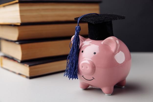 Копилка с книгами. колледж, выпускник, концепция образования.