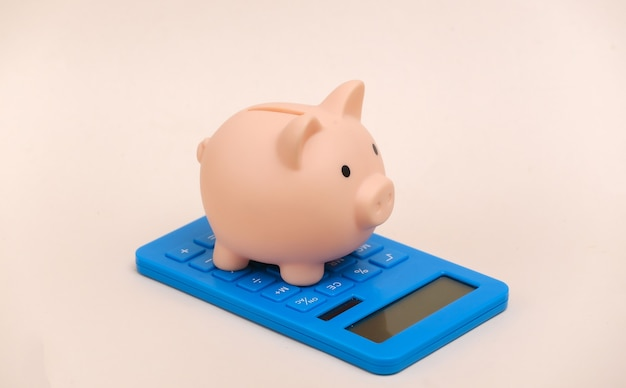 Piggy bank with calculator on beige background