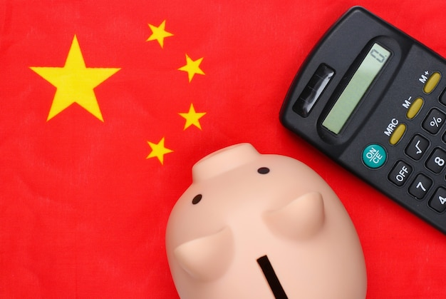 Piggy bank with calculator on flag of china.
