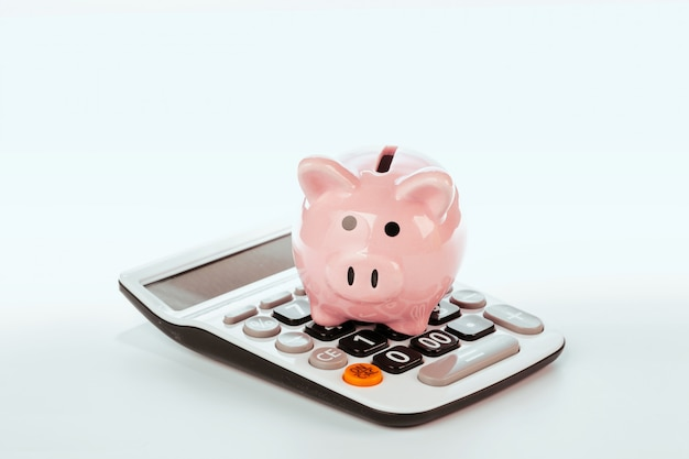 Piggy bank with calculator on white background