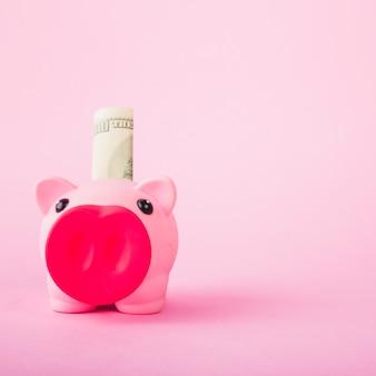 ピンクの背景に現金とピギーバンク
