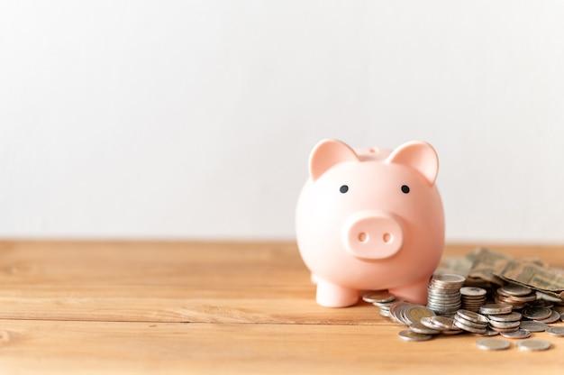 木のテーブルの上のコインと貯金箱