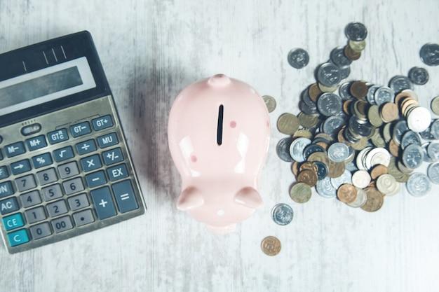 机の上にコインと電卓を備えた貯金箱