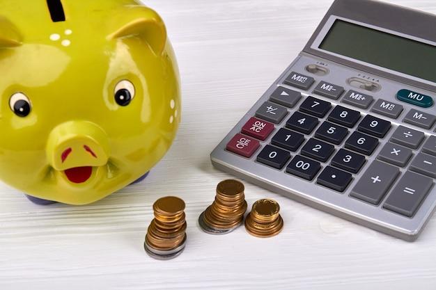コインと白いテーブルの上の電卓と貯金箱。