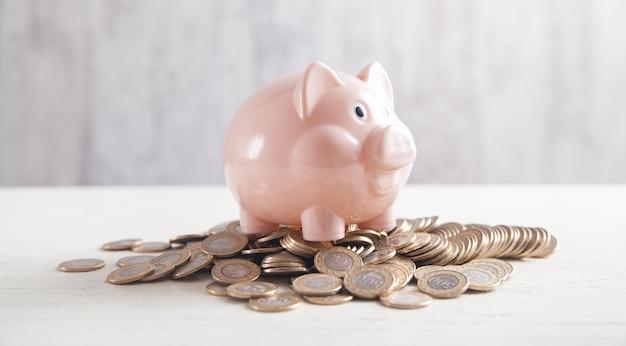 Копилка с монетами на столе. экономя деньги