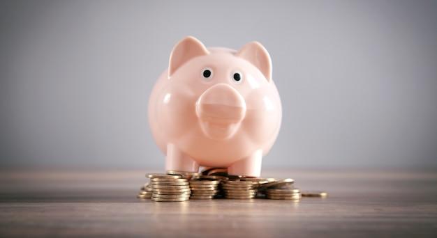 机の上にコインを置いた貯金箱。お金を節約