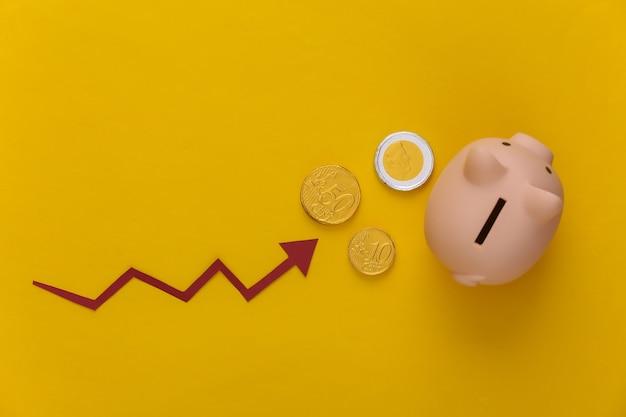 コインを入れた貯金箱、黄色に赤い成長矢印。上向き矢印グラフ。保証金
