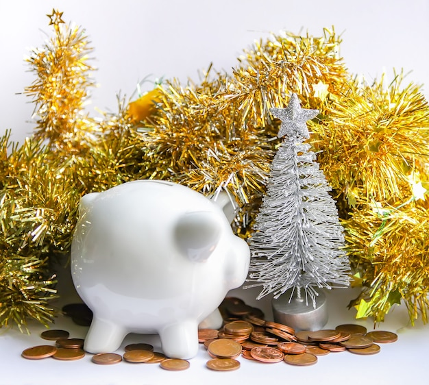 Piggy bank with coins. white ceramic moneybox with new year decor.