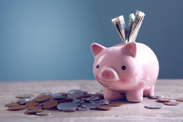 테이블에 달러 지폐와 동전이 있는 돼지 저금통