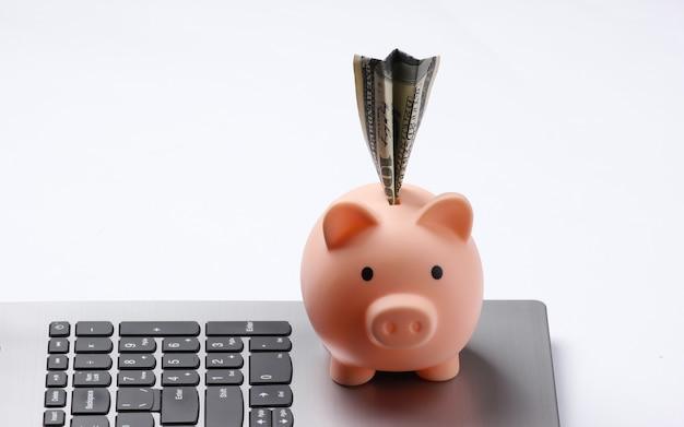 노트북 키보드 근접 촬영에 달러 지폐와 저금통
