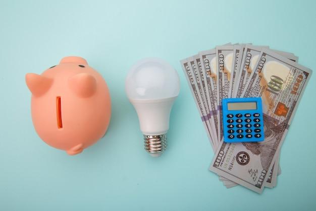 Копилка с долларовыми банкнотами, калькулятор и лампа на синем