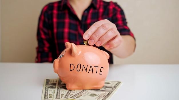 Копилка с надписью donate стоит на долларовых купюрах