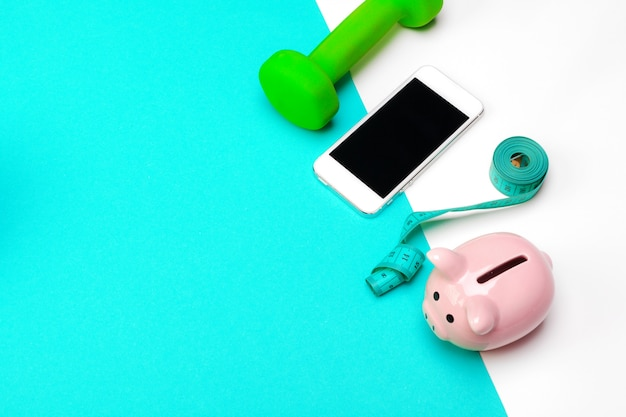 Piggy bank with dumbbells on turquoise background