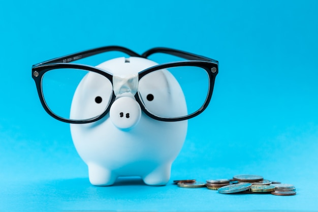 Piggy bank with glasses on blue