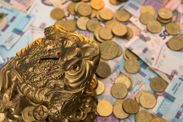 Копилка с золотыми монетами лежит на украинских банкнотах. 500 и 1000 гривен. новый. грн. концепция сохранения
