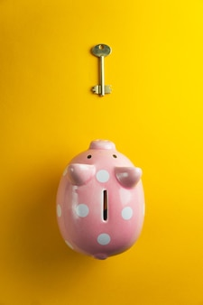 Piggy bank with golden key on yellow background