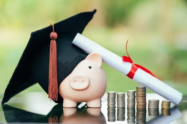 Piggy bank with graduation cap on black glass floor,money saving concept.