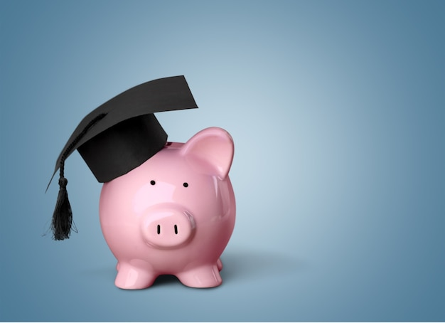 Piggy bank with graduation hat on light background