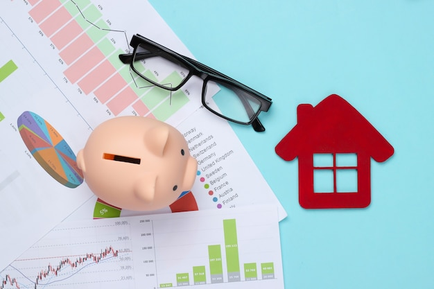 Piggy bank with graphs and charts, house figure on a blue. housing cost analysis