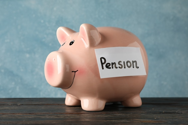 Piggy bank with inscription pension against blue surface