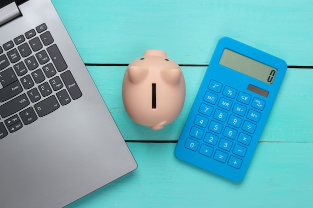 Piggy bank with laptop, calculator on blue wooden surface. make money online or internet business concepts. top view. flat lay