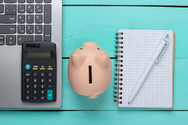 Piggy bank with laptop, calculator, notebook on blue wooden surface. make money online or internet business concepts. top view. flat lay