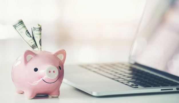 Piggy bank with laptop on the desk