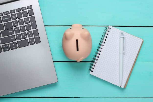 Piggy bank with laptop, notebook on blue wooden surface.  make money online or internet business concepts. top view. flat lay