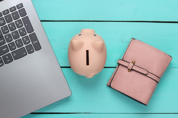 Piggy bank with laptop, wallet on blue wooden surface.  make money online or internet business concepts. top view. flat lay